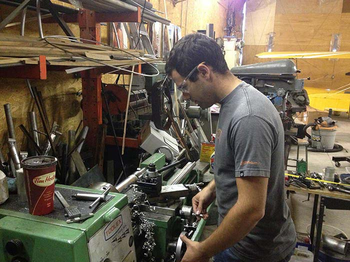 Cameron turns an aluminum part of the Dummy Rotor Axle on the lathe at Cleland Instruments' shop.