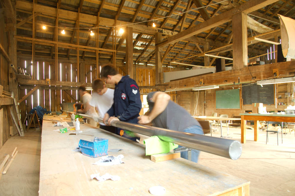 Team members polish the aluminum tapered tube used to lay up carbon fiber structural members.