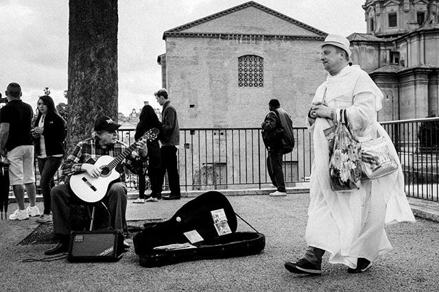 """""""Shall I ignore him?"""" (#Rome, #Italy 2014) While preparing this image for instagram I wondered if the man with his hand crossed is a real priest? Is he actually praying or just pretending to, so he can ignore the street musician? . . . #praeteriens #blackandwhitephotography #blackandwhite #bnw #bw #monochrome #paterson #Fujifilm #X100s"""