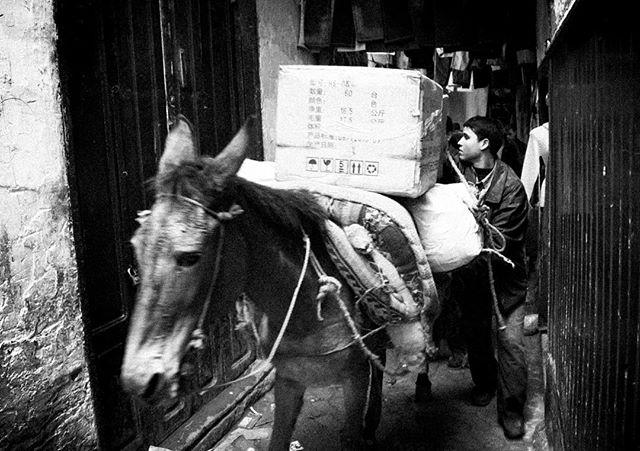 """On time delivery"" (#Fez, #Morocco 2005) In the narrow streets of Fez, there is no room for cars or scooters. Deliveries are done by man- or animal power. Shot on one of my first digital cameras, the Nikon D70s. Struggling in Lightroom to get that good old analog look. . . . #praeteriens #streettogs #streetphotography #streetphotographyinternational #blackandwhitephotography #blackandwhite #bnw #bw #monochrome"