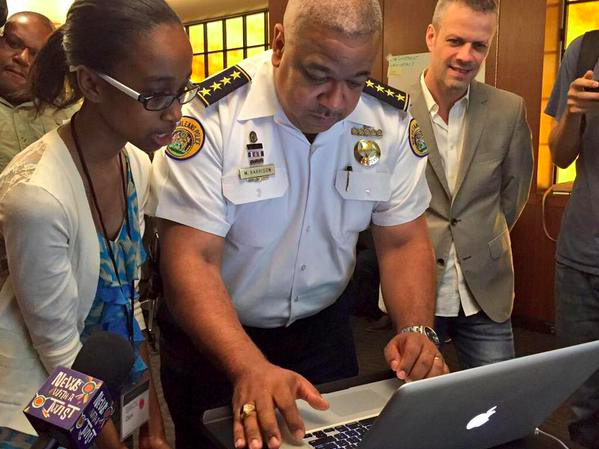 Fifteen-year-old Grace Clark teaches New Orleans Police Superintendent Michael Harrison how to write his first line of code. (Official NOPD photo by Tyler Gamble via Denice Ross)