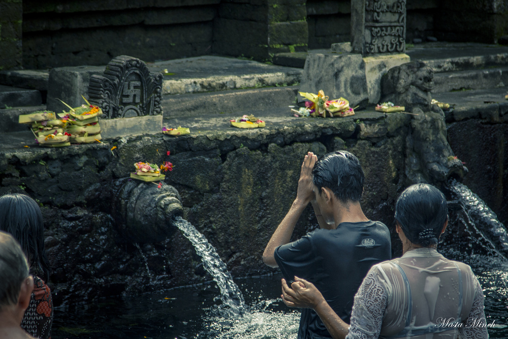 Bathing in the sacred spring water and praying for many blessings.