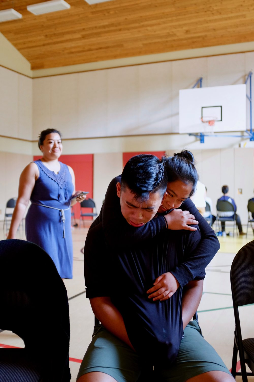 Mentor M-jay Frias hugged by mentee (and sister) Mica as facilitator Monica Batac looks on. Photo by J. Austria.