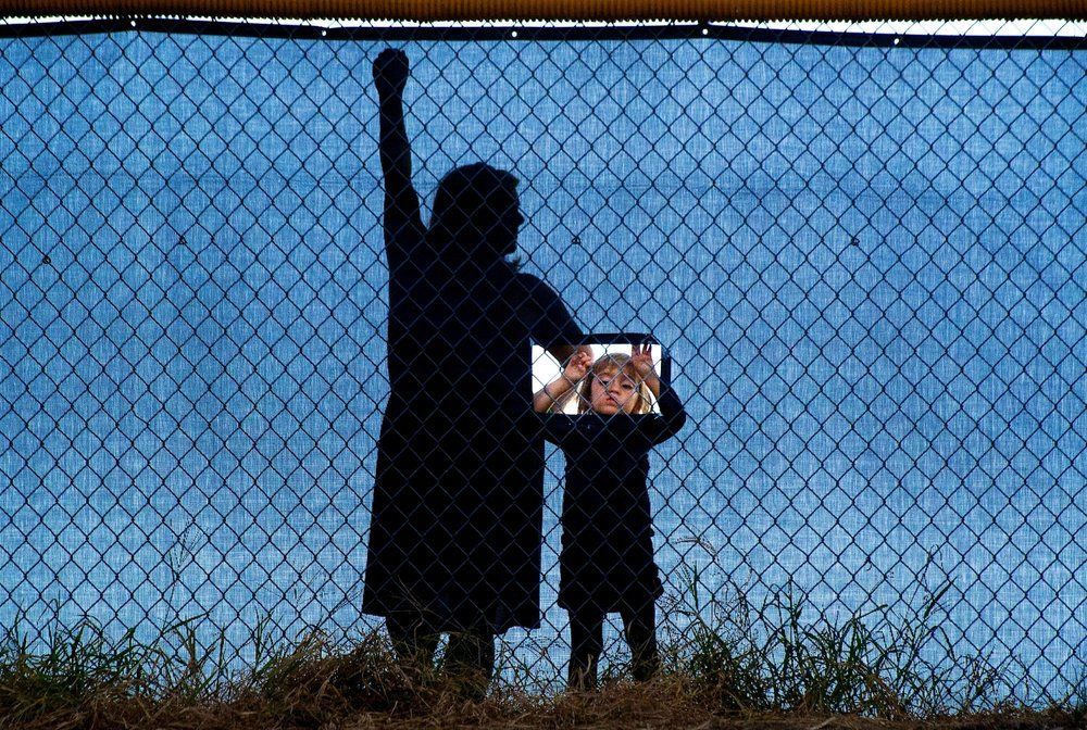 Mindy Mohlenbrok, left, waits behind a fence as her daughter Kendall Mohlenbrok 3 peers through a hole to watch a football game at Del Oro High School in Loomis on Friday, August 24, 2012.