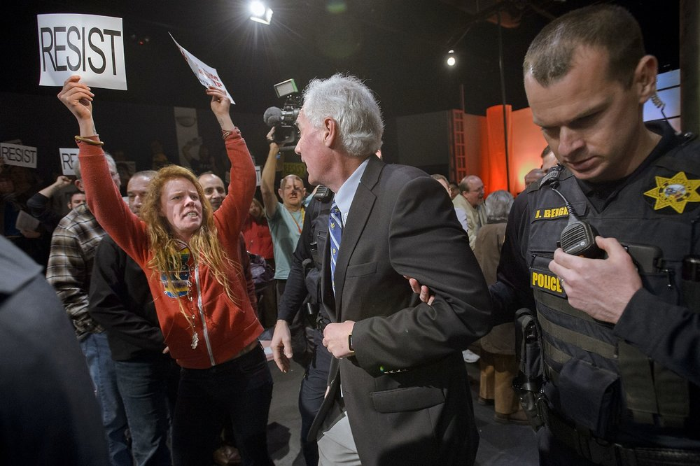 Congressman Tom McClintock (R) 4th District California, center, is escorted by Roseville Police through a hostile audience from the Tower Theater in Roseville on Saturday, February 4, 2017.  McClintock held a town hall meeting at the theater and hundreds of anti Trump demonstrators chanted slogans and carried signs outside. The swollen crowd eventually blocked traffic on Vernon Street.