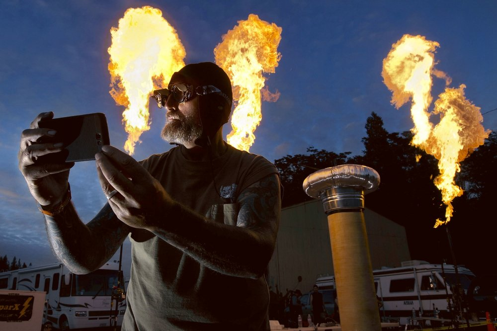 """""""Wild"""" Bill Hill takes a photo of himself in front of large bursts of fire during the 'Fire and Steel' event in Colfax on Saturday, June 14, 2014"""