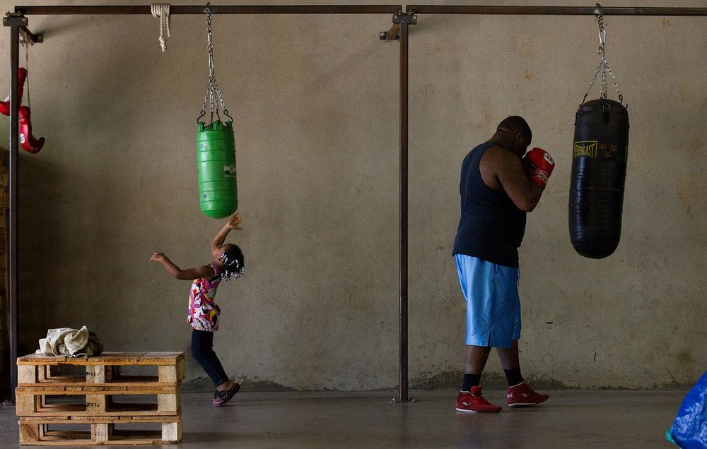 Ja'Niya Haley 3, left, mimics her father Cassius Haley as he works out at Main Event Mateen Boxing Club in Sacramento on Thursday, June 16, 2011.