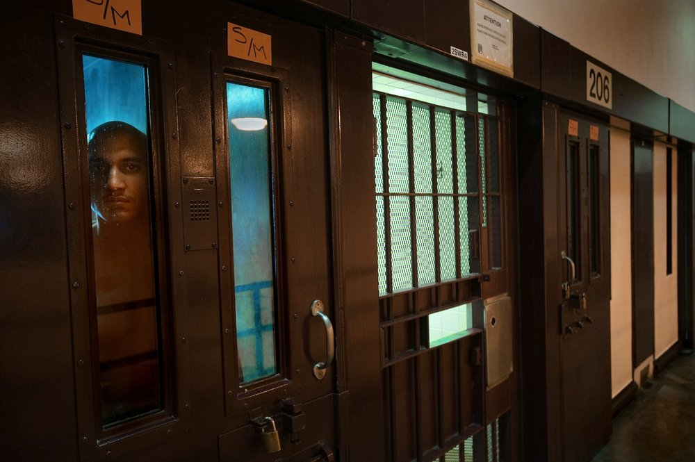 Prison inmate Joell Polanco, at left, peers from his cell in the behavior management unit at the Substance Abuse Treatment Facility in Corcoran on Thursday, March 25, 2010.