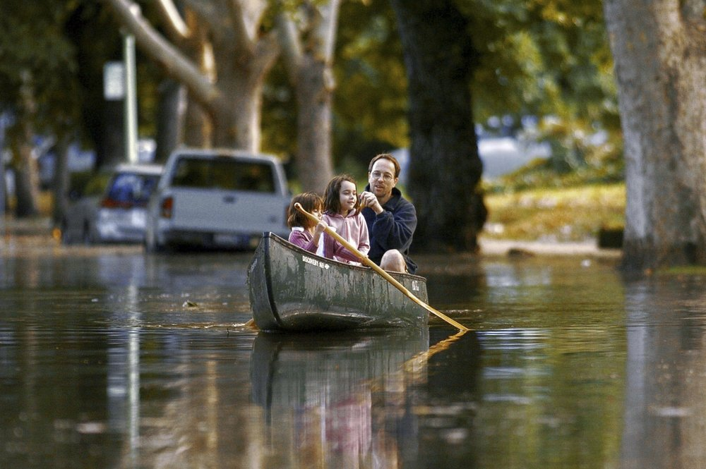 Lily Brown 5, left, her sister Emma Brown 6, and their father Doug Brown paddle a canoe up 38th Street near Folsom Blvd in Sacramento on Sunday September 19, 2004. Unexpected heavy rain flooded many parts of the midtown, and downtown areas of Sacramento.