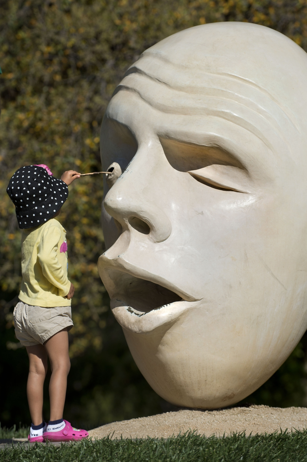 "Reese Jackson 3 of Sacramento pokes a twig into the eye of a sculpted ""Egg Head"" during the 100th annual Picnic Day at UC Davis in Davis on Saturday, April 12, 2014."