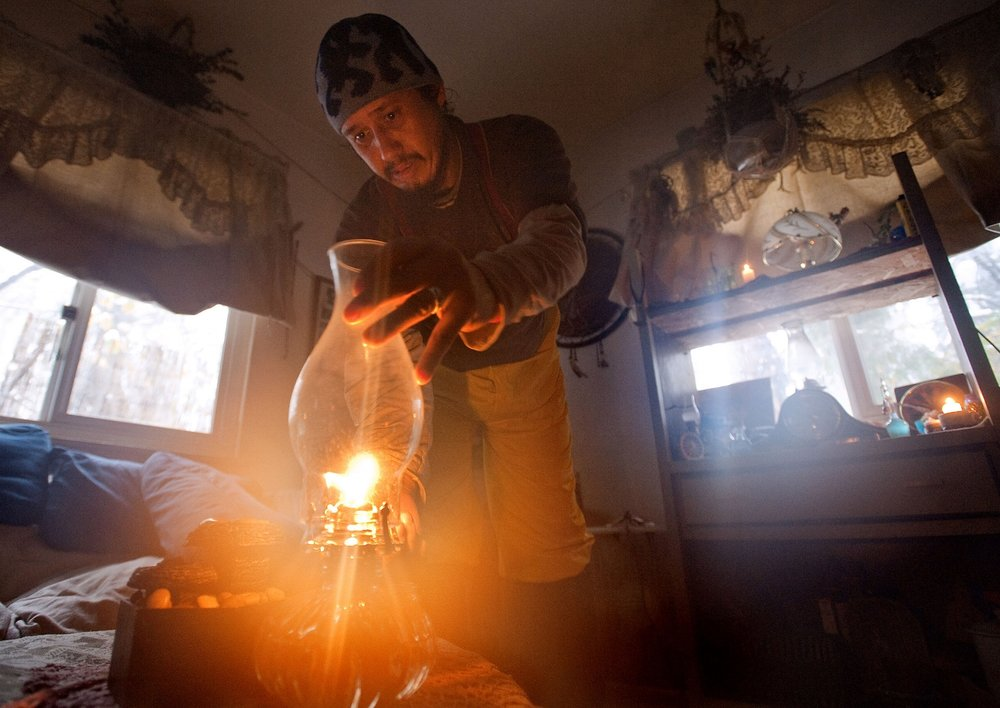 John Dunnigan lights an oil lamp in his home in Pollock Pines on Tuesday, November 23, 2010. Dunnigan and his family had been without power for the past few days due to heavy snow and relied on candles and oil lamps to light the house.