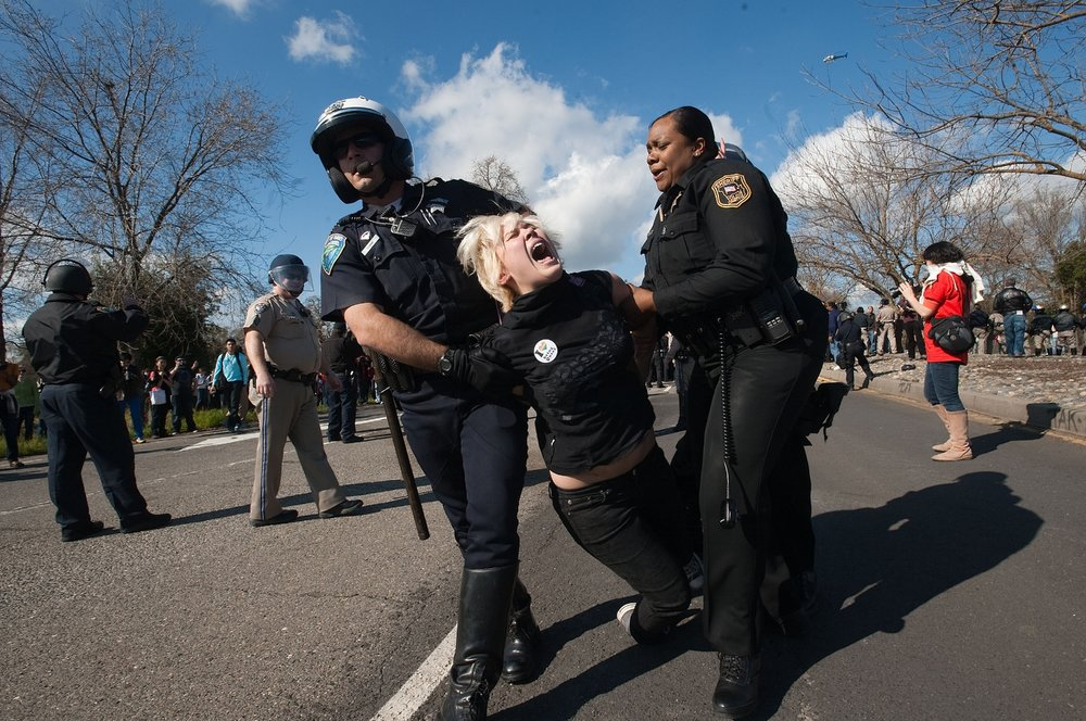Davis Police and Yolo County Sheriff deputies carry away 5th year UC Davis student Laura Mitchell as students demonstrate at the UC Davis campus on Thursday, March 4, 2010. The students tried to block traffic on Interstate 80