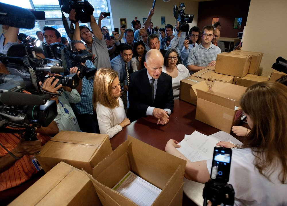 California Governor Jerry Brown delivers signatures for a tax measure to the county registrar's office in Sacramento on Thursday, May 10, 2012. HIs wife, First Lady Anne Gust Brown is with him on the left.