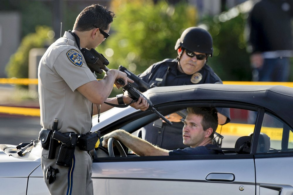 A California Highway Patrol officer and Roseville Police stop a motorist as he leaves a neighborhood where a search continues for a man suspected of shooting an Immigration and Customs Enforcement officer in Roseville on Friday, October 25, 2013. Inbound traffic was closed, but residents leaving the area where stopped, and their vehicles briefly searched to make certain the armed suspect did not escape.