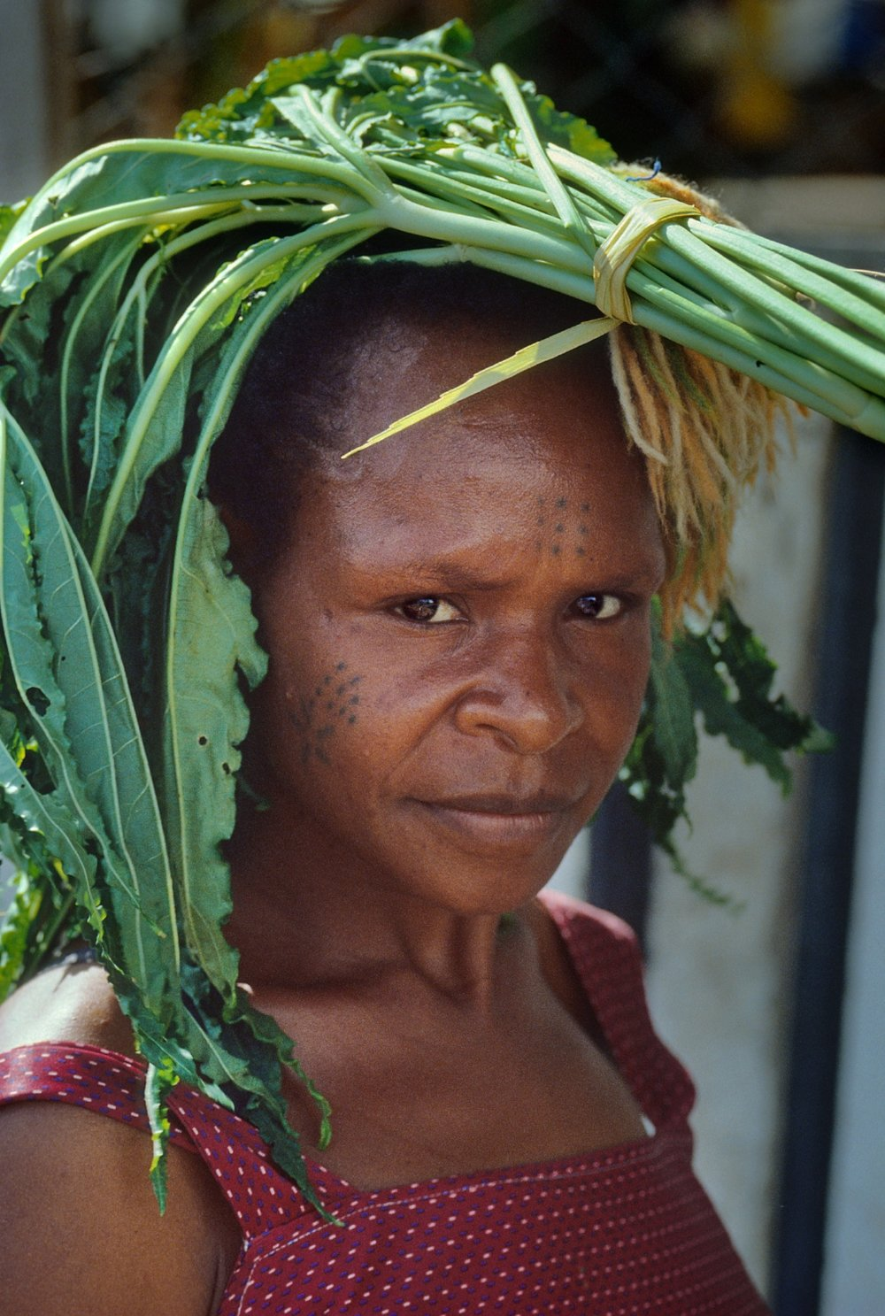 Her arms full of other groceries, an unidentified woman carries food on her head in Port Moresby, Papua New Guinea.