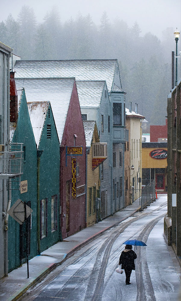 A woman walks along Stage Coach Alley behind the shops on Main Street in Placerville, CA on Friday, February 25, 2011.