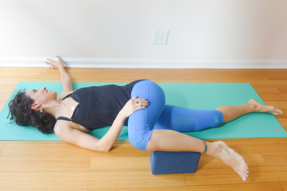 SUPINE TWIST: This pose is great to release the low back and the outer hip. As you twist across your midline, keep your shoulders on the floor, make sure you have a block under your crossed shin in order to maintain the clean line between your knee and your hip.