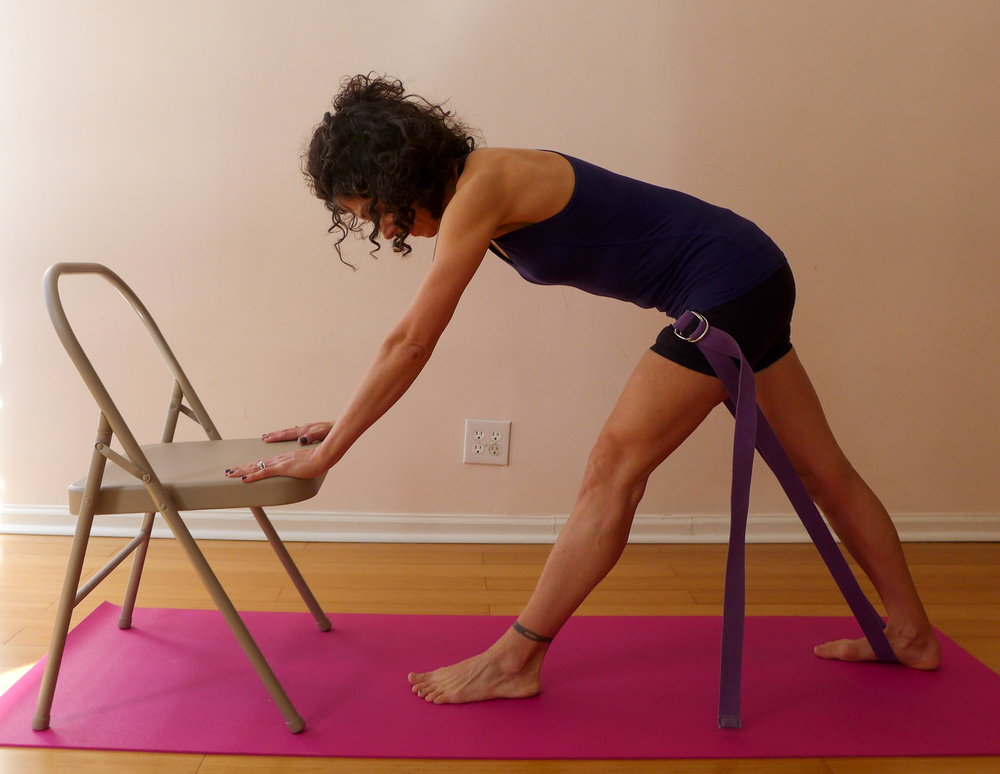 PYRAMID POSE WITH PROPS: Press down into the chair in order to move your hips back in space. This will help lengthen the hamstrings and calves while releasing the low back. Add the strap to create traction of your front leg's thigh bone moving back in space. Hold for 5 breaths, change sides.