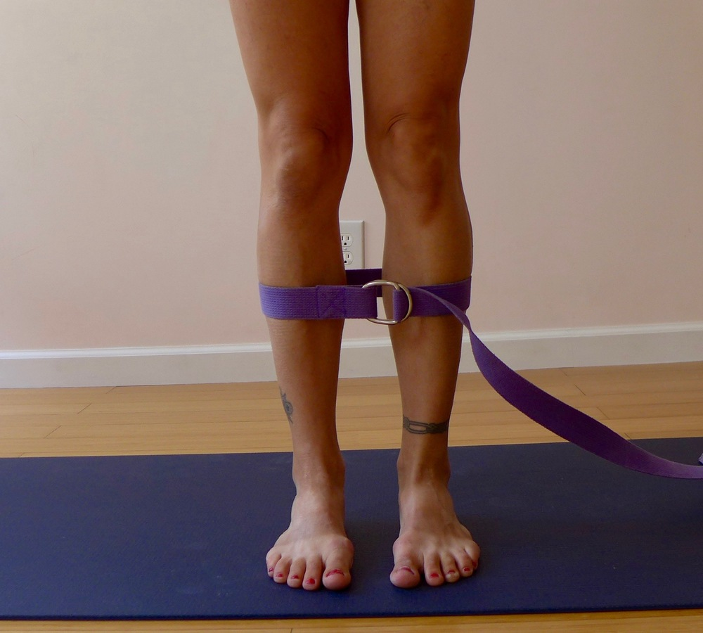 By strapping the shins, we track the big lower leg bone, the tibia.  This bone is often the missing piece from the feet to the hips - by aligning it, we create a more solid foundation for the pelvic girdle and hips.  How to do: Start in mountain pose.  Cinch a yoga strap around the thickest part of your calves. Ground the inner and outer feet evenly, then push your lower legs into the strap. Count to five, then release. Keep the inner feet grounded and the knees unlocked.