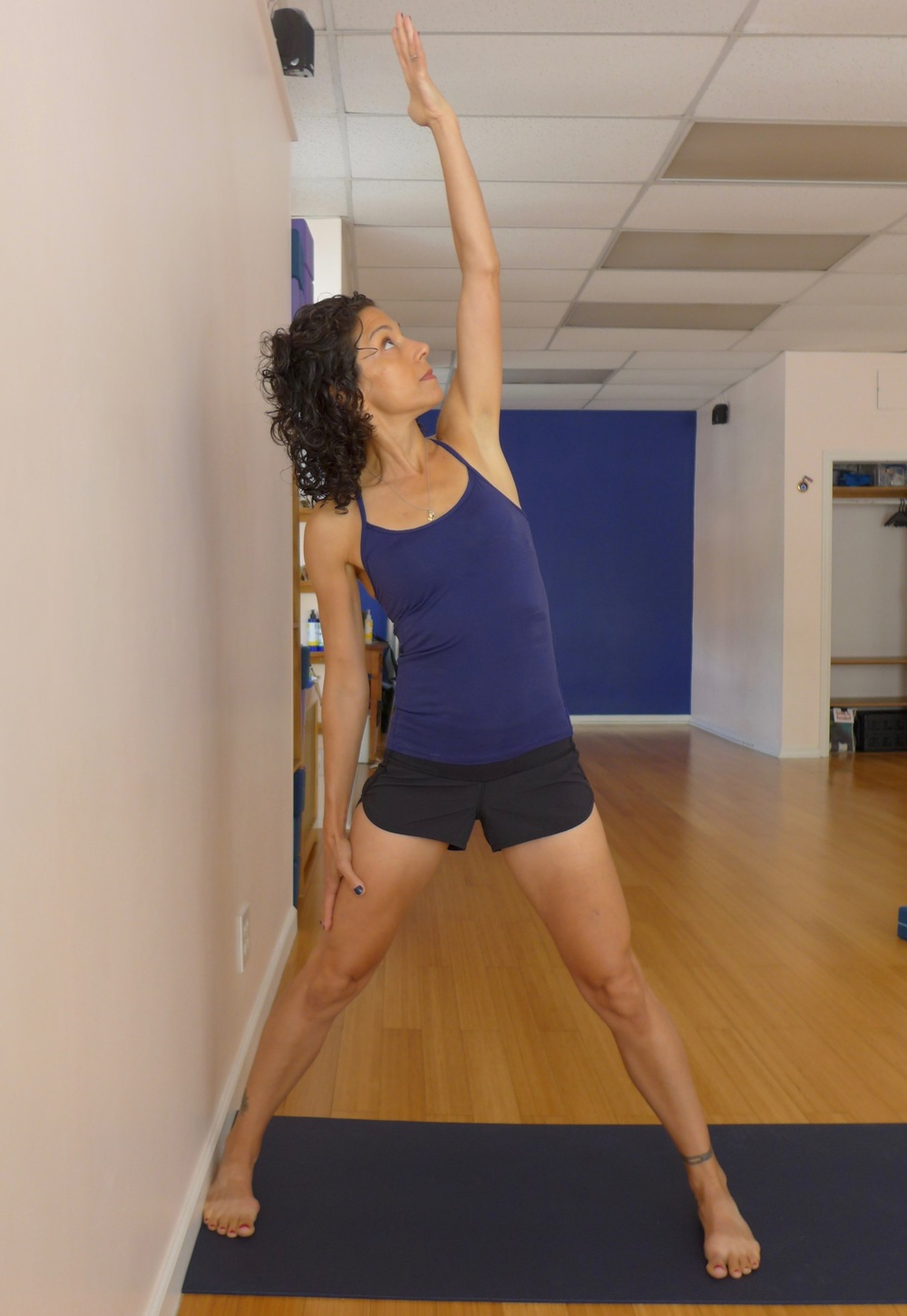 Triangle with feet parallel: In this version of triangle, your feet are parallel to create more pelvic stability. Press the outer edge of your foot into the wall, and side bend towards the wall. Keep your quadriceps and brace your abdominal wall.  You can also side bend away from the wall.