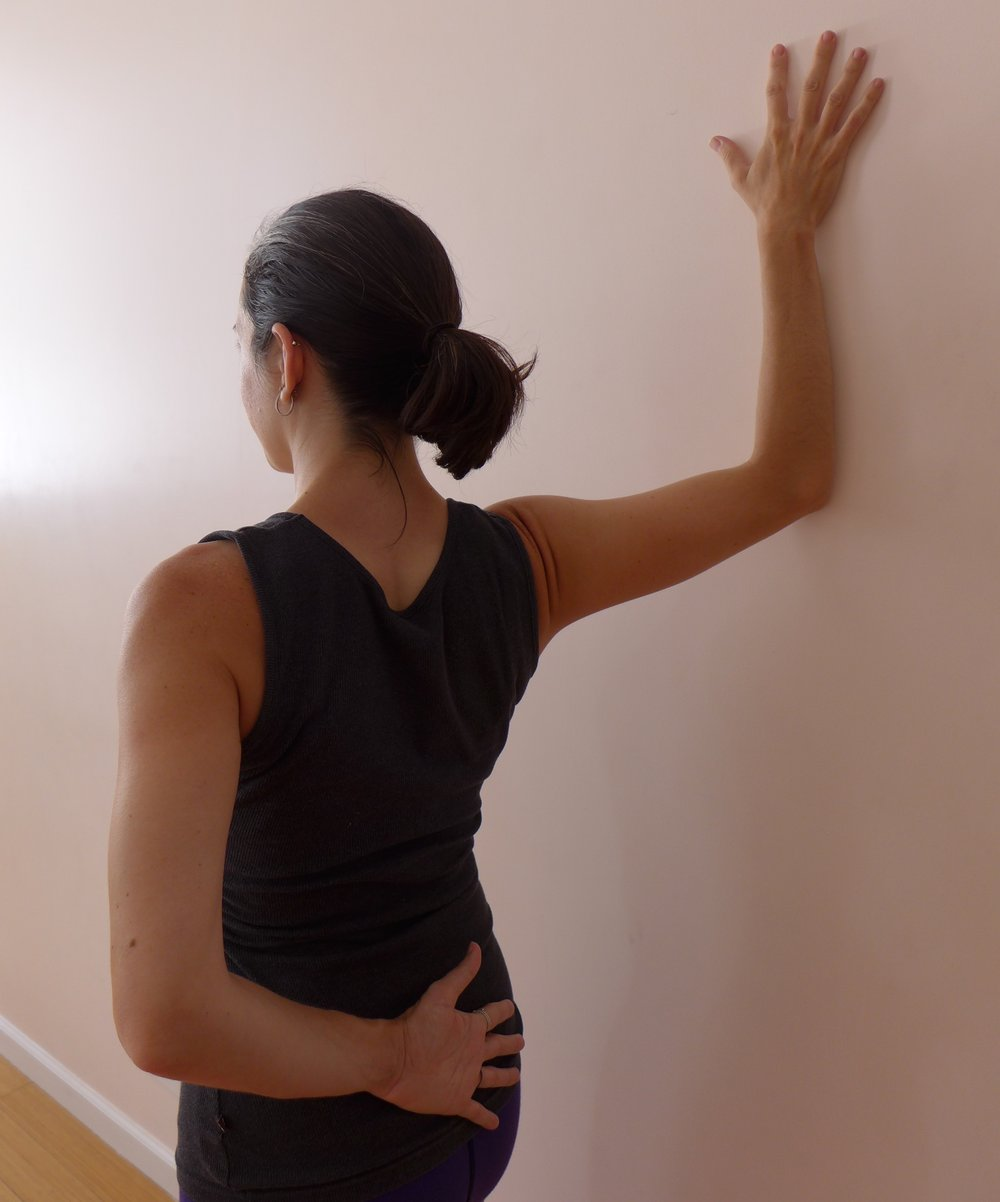 Pec Stretch at Wall:  An oldie but a goodie! Place your forearm at the wall behind you, work to keep the elbow at the height or higher than the shoulder. As you turn your body slightly away from the wall, press your forearm into the wall to keep the head of the humerus (upper arm bone) integrated with the shoulder joint so you get the stretch in the pecs and biceps line and not in the joint itself.