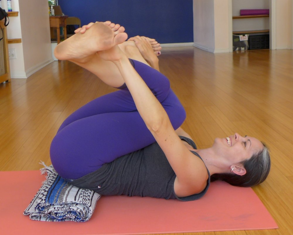 Supine Gomukasana:  You may not want to do this one until 12 - 24 weeks after the birth. This is a great pose for those hip muscles that get tight very quickly.  The blanket under the hips allows for and easy access to grabbing the feet or ankles. Draw the feet out to the sides and hug the knees in towards the chest.