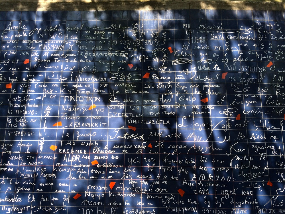 I didn't know what this was when we stumbled onto it in a park in Montmartre. It's The  Wall of Love – Mur des je t'aime . The I Love You Wall, where the words I love you are written in 300 of the worlds languages.