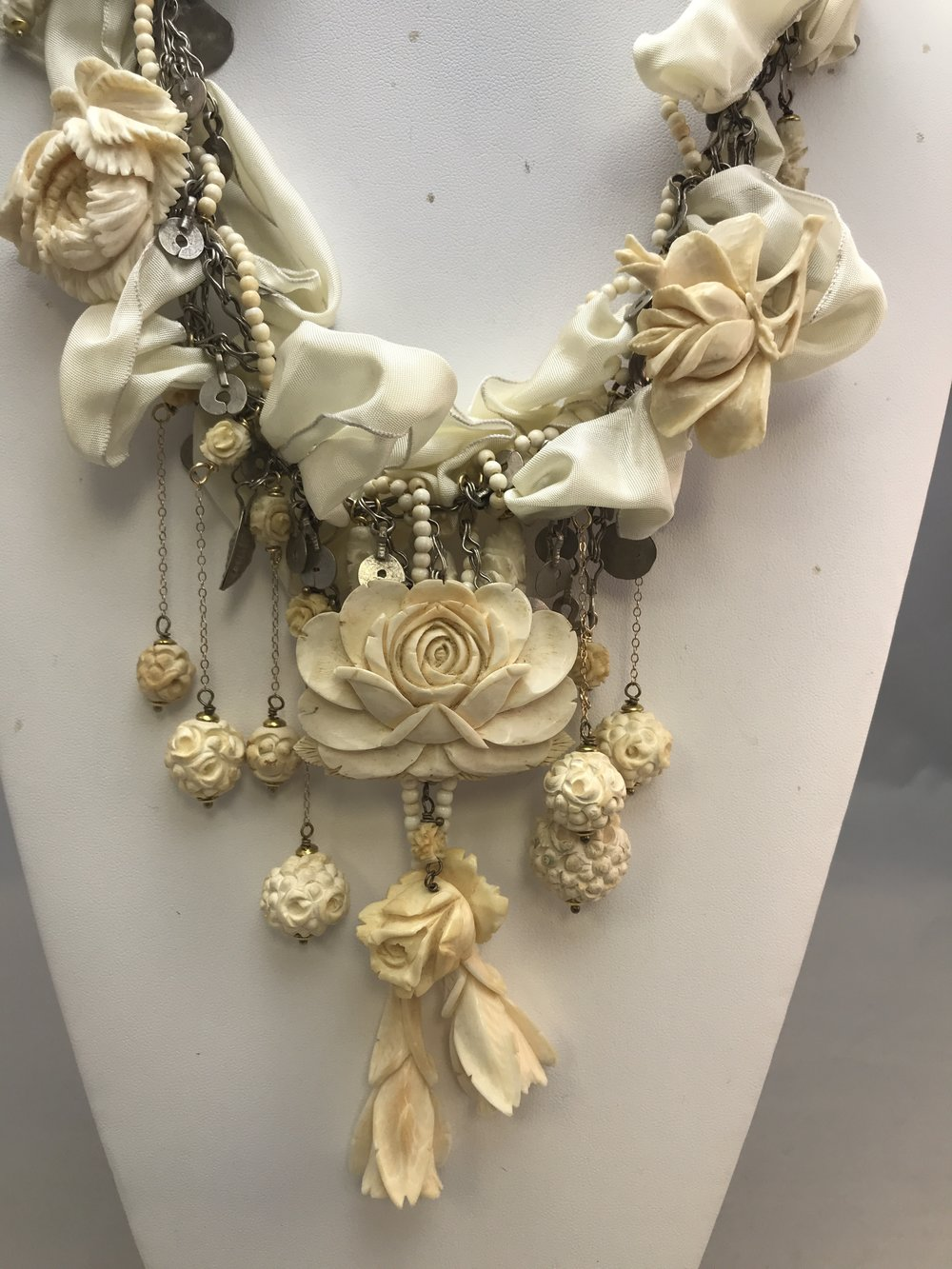 This is a combination of carved Ivory broaches, carved, ivory beads, a cream silk ribbon, on an antique Turkish bellydancing chain.
