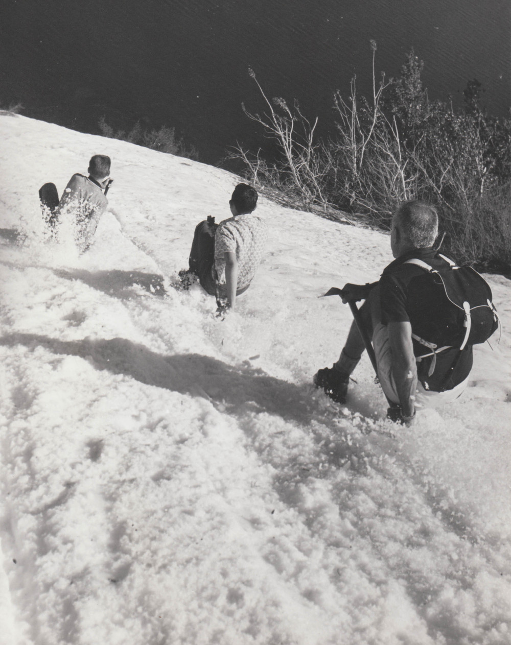 Louis teaching two boys the art of glissading—how to quickly and safely descend a glacier.