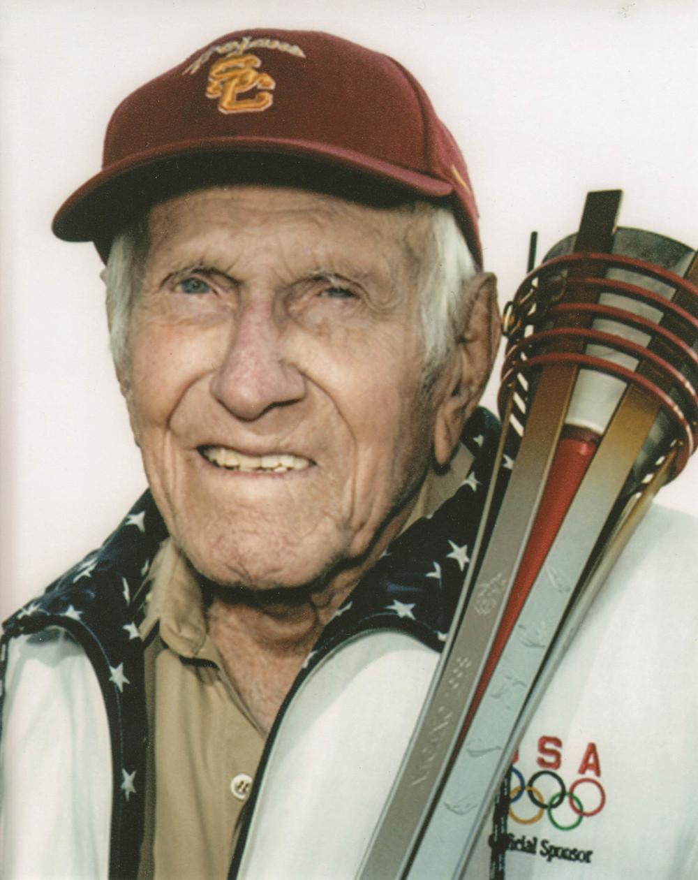 Louis Zamperini holding the Olympic torch he carried in the 1998 Nagano Winter Olympics.