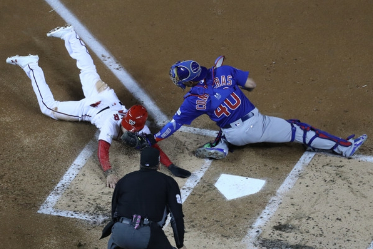 Chicago slid past Washington by a matter of inches in Game 5 of the NLDS. (Photo by Rob Carr)