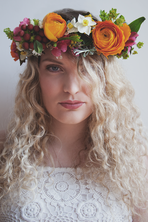 Blonde lady wearing a lovely floral headdress of natural flowers.