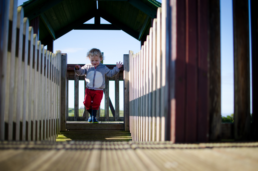 My boy running along a playground bridge