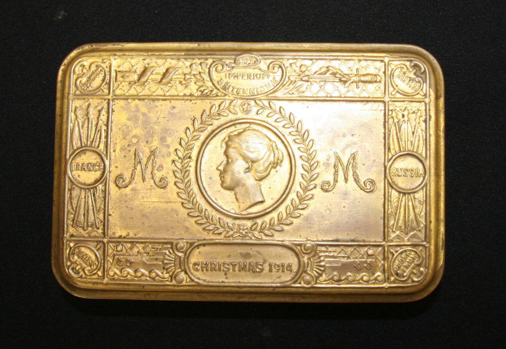 The Princess Mary tin is a flat rectangular gold coloured tin, stamped on the lid with profile of a young woman's head at the centre, letters M at left and right. Border of the lid is stamped with 'Imperium Britannicum', 'Christmas 1914'  then the nations, Belgium, Japan, Russia, Monte Negro, Servia, and France.