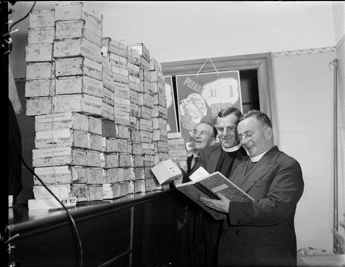 Figure 7: Wellington City Mission ministers Reverend Harry Squires and Reverend Keith Elliott prepare boxes for the Wellington City Mission appeal day with Mr G Clarke. Source: Evening Post Collection, Alexander Turnbull Library, ref: 114/312/05-G. URL: http://mp.natlib.govt.nz/detail/?id=62338