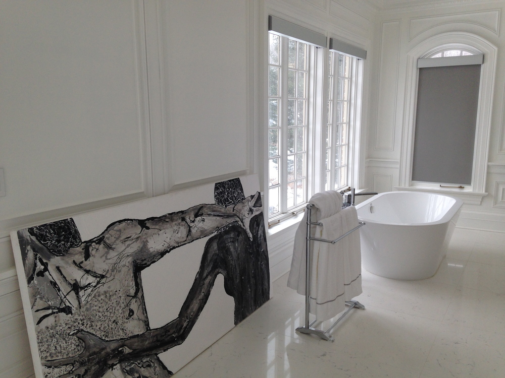 graphic art pops in this all white master bathroom