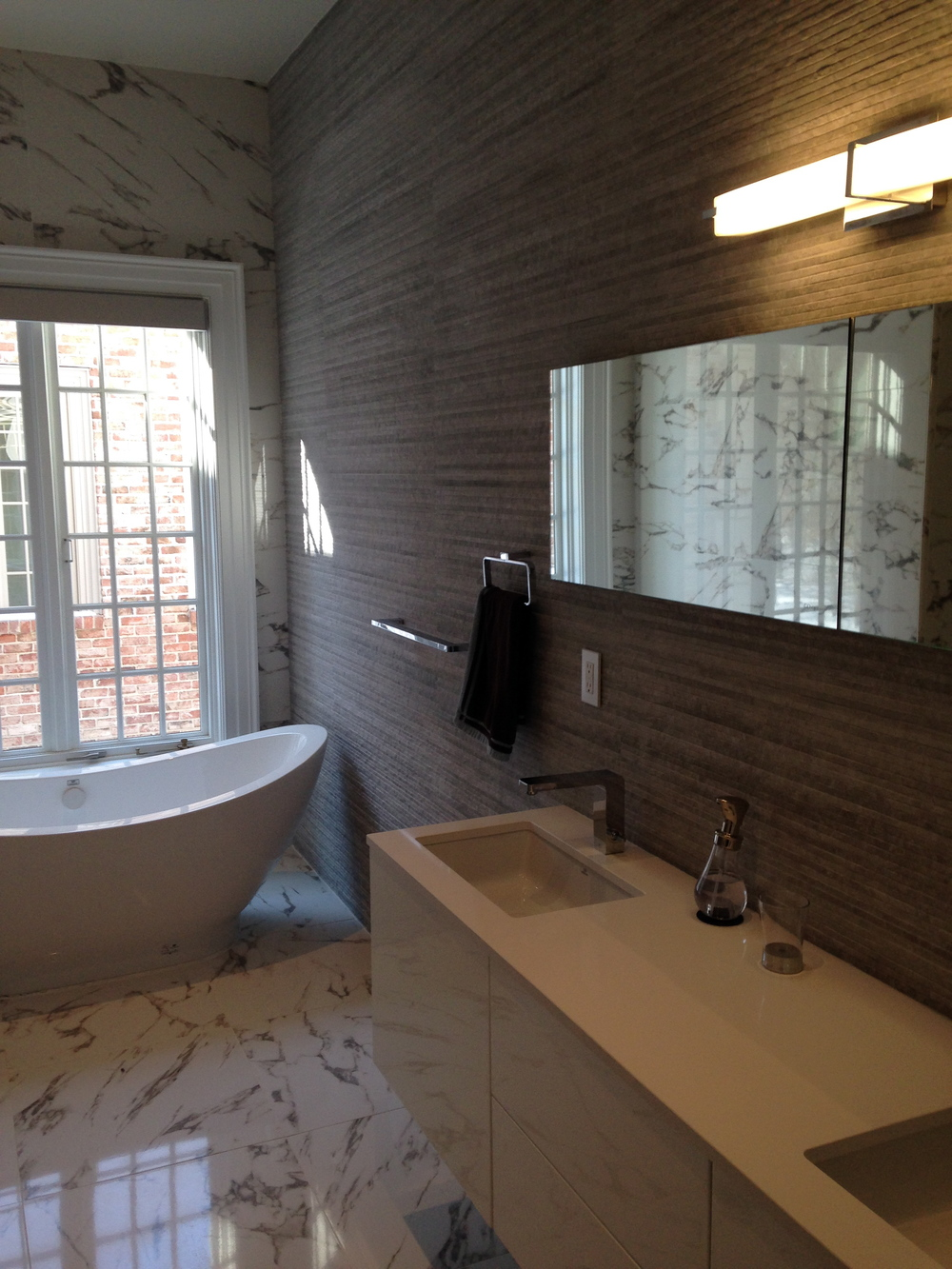 Textured wall tile and smooth marble on the floor of this contemporary bath help to create a spa like feel.