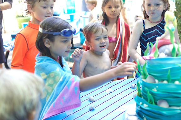 Violet, Archer and Guests admire the Tails and fins cake!