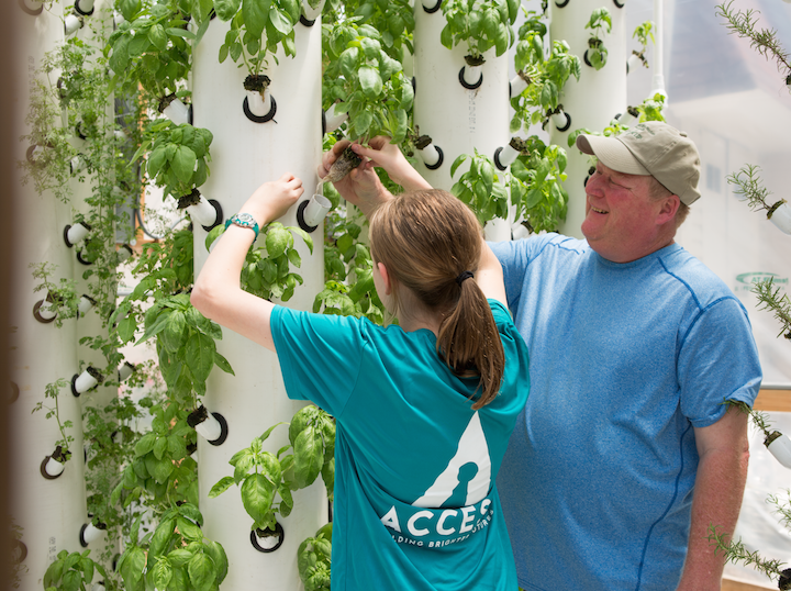 Access Academy student works with a horticulture expert to plant herbs in the soil-free, aeroponics growing system. photo by rett peek.