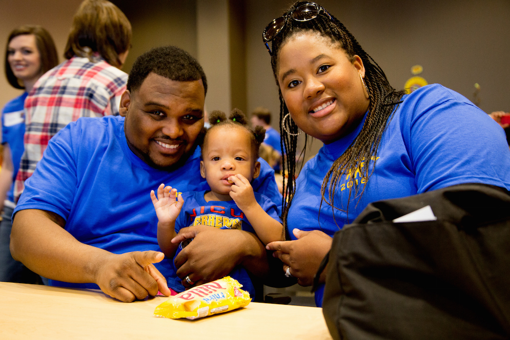 Seventeen-month-old Talyn Addison Farris (center) sits with her parents, Talya and Antonio, while enjoying a bag of Vanilla Wafers. She was born at 26 weeks and spent 103 days in the NICU.