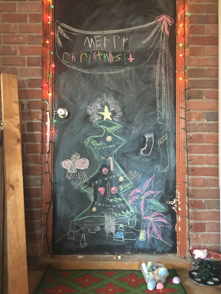 We have a chalkboard door that we rotate seasonally with a new drawing. It's so fun seeing how my kids' drawing skills develop season to season. The Christmas drawing is always a favorite