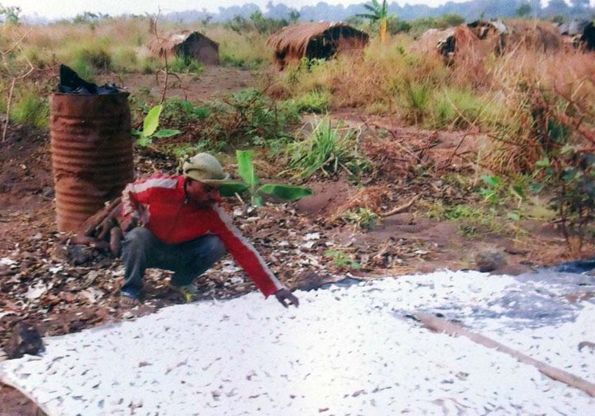 Den fuktige manioken spres utover slik at den skal tørke i solen. I bakgrunnen ser man hyttene som folket bor i mens de arbeider på åkeren.