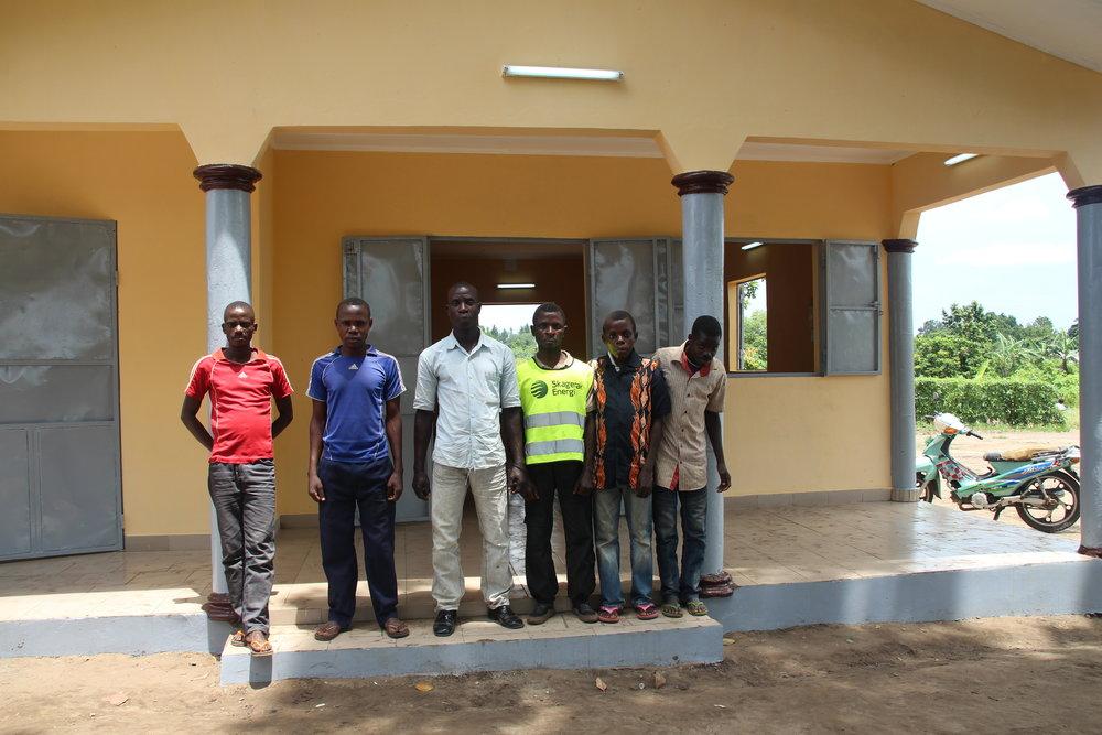 De 6 stolte murerne fra urfolket foran det flotte administrasjonsbygget på Ngo.