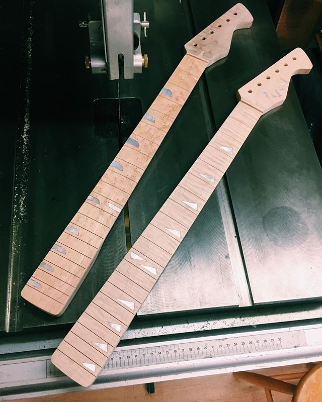 "Congratulations, it's twins! On the right we have a plain maple neck, 12"" diameter flame maple fretboard with geometric mother of pearl inlay, which now sports 2.5mm frets. This one's destined for the white tele. And on the left a flame maple neck that's been lying in waterlogged soil on a US farmstead for 20 years, 10"" diameter birdseye maple fretboard with curvilinear mother of pearl inlay, which now sports 2.4mm fretwork ... but which guitar could this be destined for? Well that's for you to wonder with casual disinterest at, and for me to know 😎"
