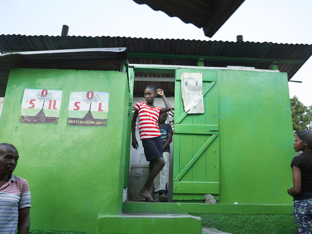 A young woman exits a SOIL public toilet in the impoverished community of Shada, Cap-Haitien.