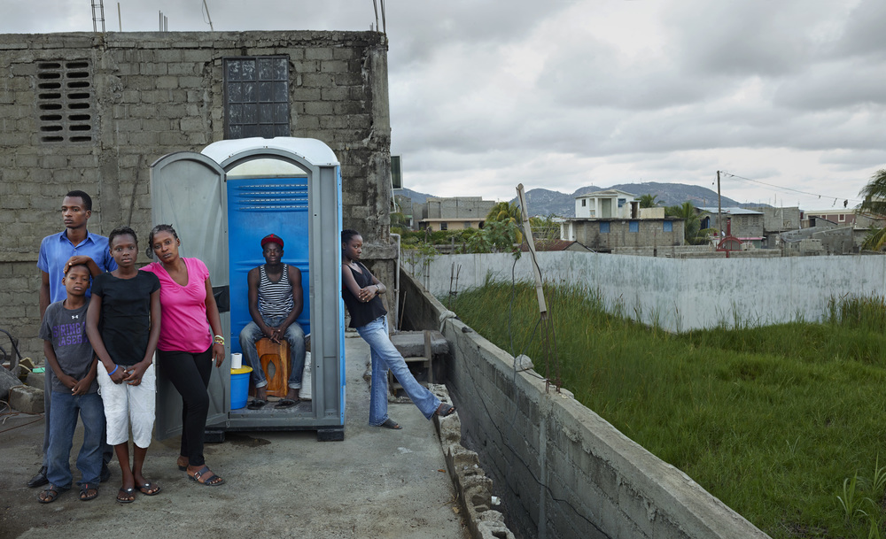 Marline Jean with five of her children on the roof of their home, where their SOIL toilet is located inside of refurbished porta potty. Marline lives in the neighborhood of Avyasyon in Cap-Haitien, Haiti.