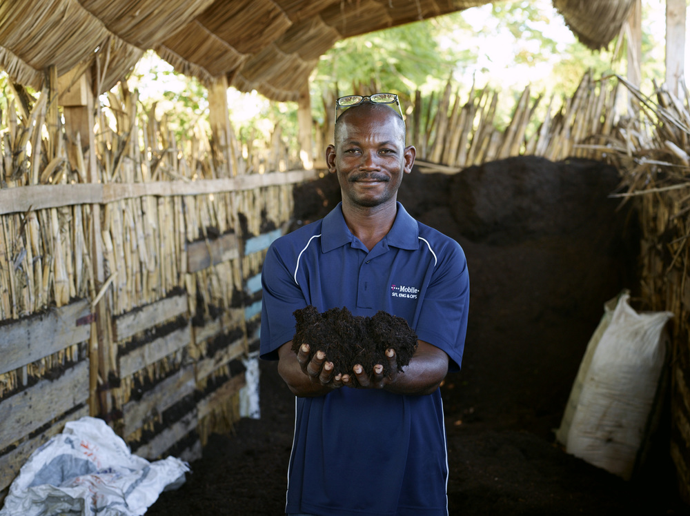 Job Etienne, the leader of SOIL waste treatment at Mouchinette team holds the finished compost in his hands. Cap-Haitien, Haiti.