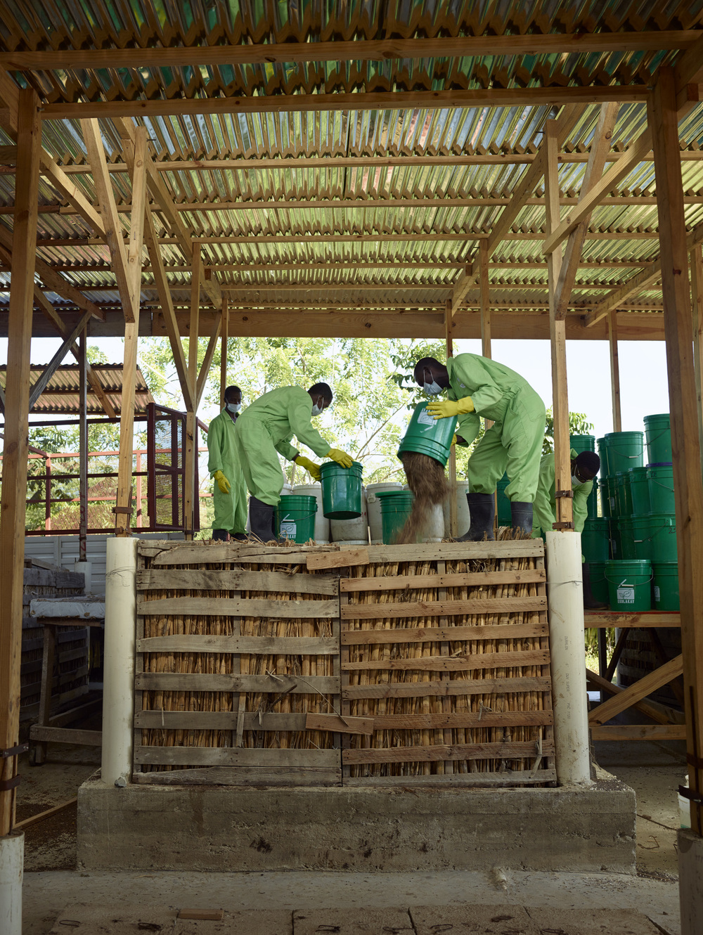 SOIL employees pour containers including human feces to compost bins at the Mouchinette treatment center, Cap-Haitien, Haiti.