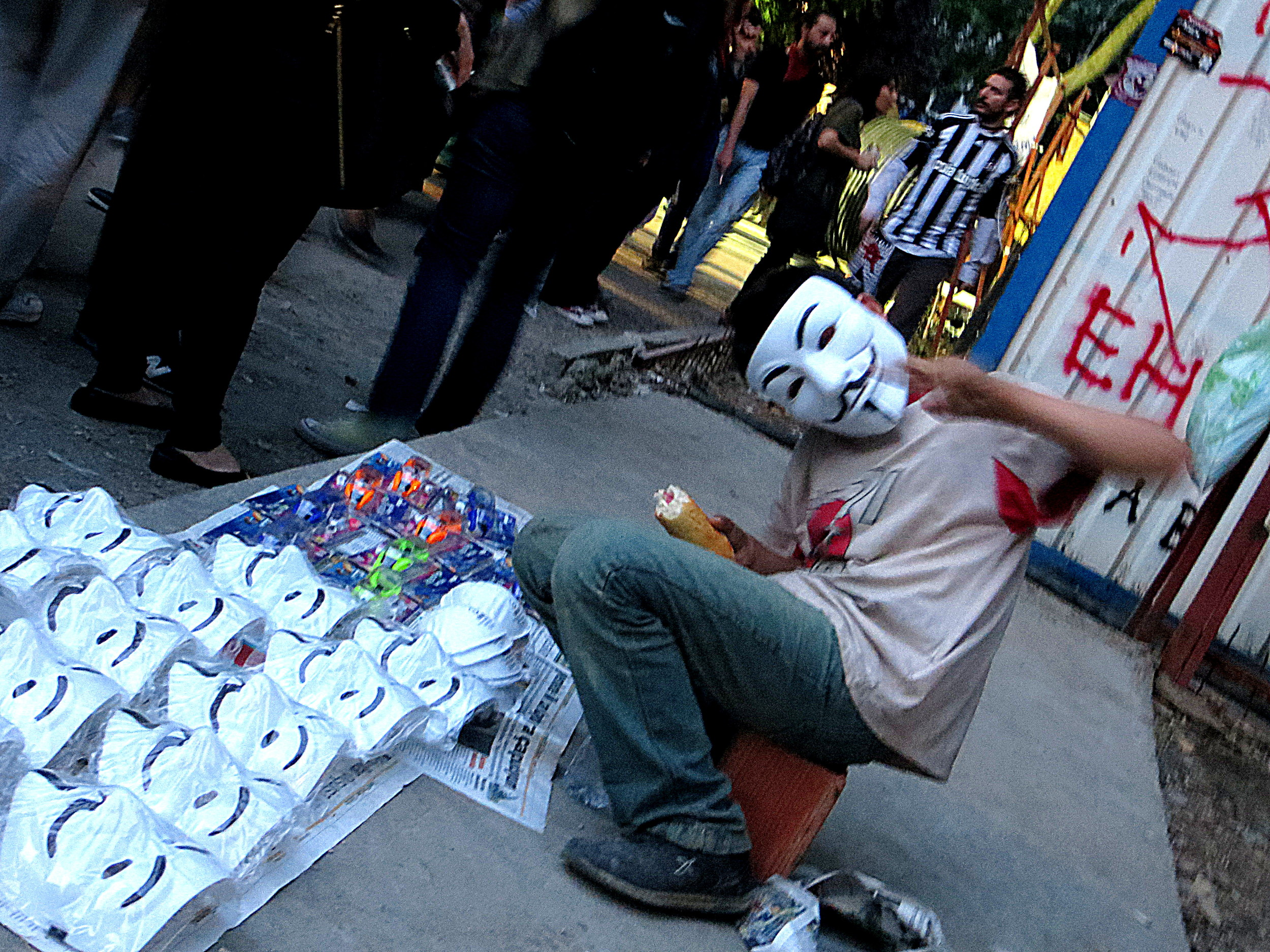 A kid sells Guy Fawkes masks in Gezi Park.
