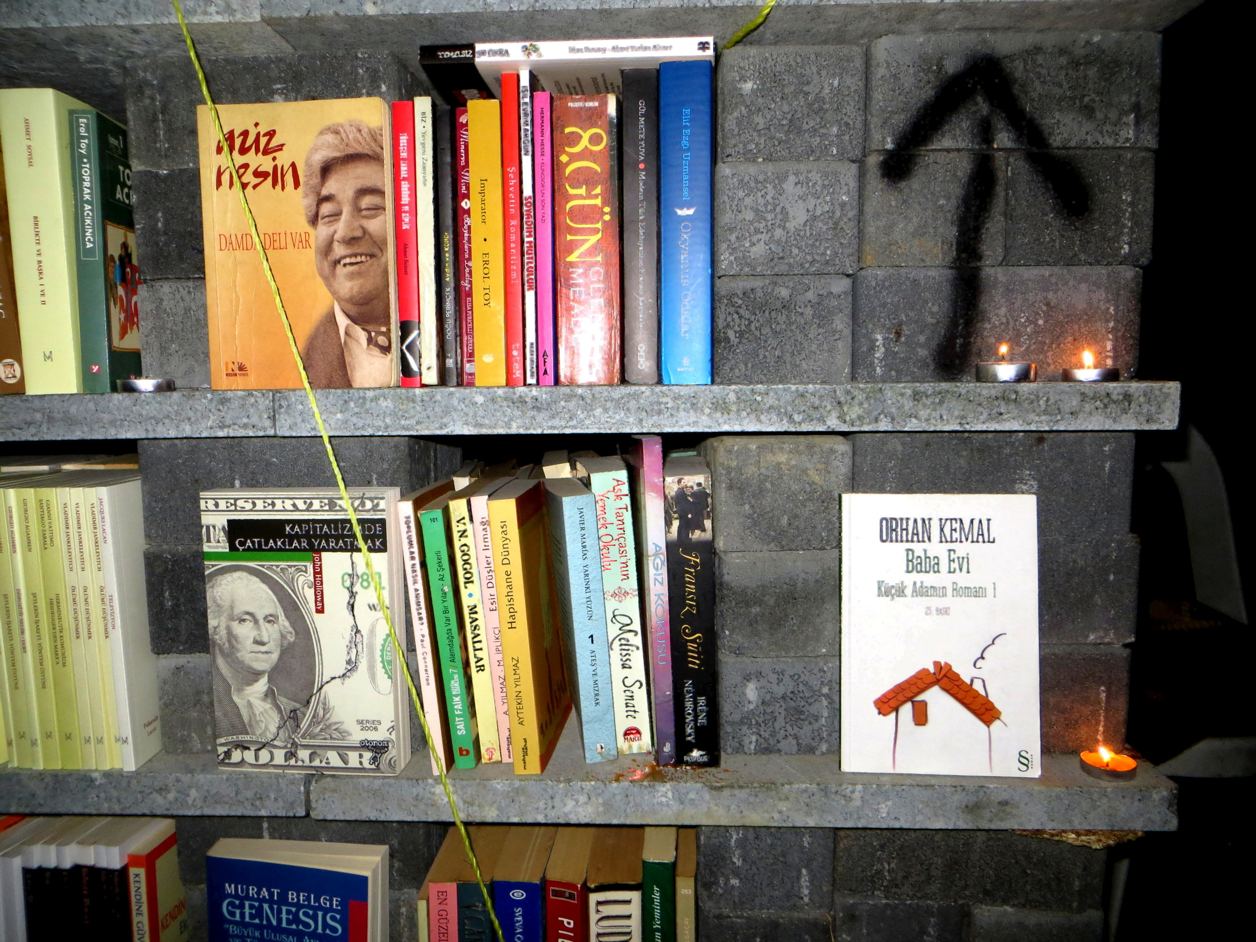 A candlelit library, stacked with revolutionary books, in Taksim's Gezi Park. Click to read more.